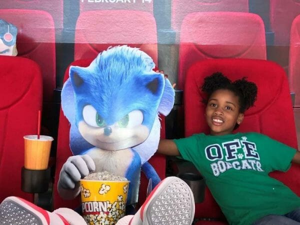 Picture of a cardboard Sonic the Hedge Hog and Harper L Ferguson at the movie theater sitting in a chair.