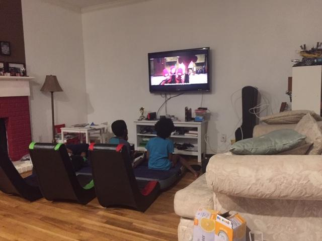 3 kids sitting in rocker gamer chairs watching a movie on television